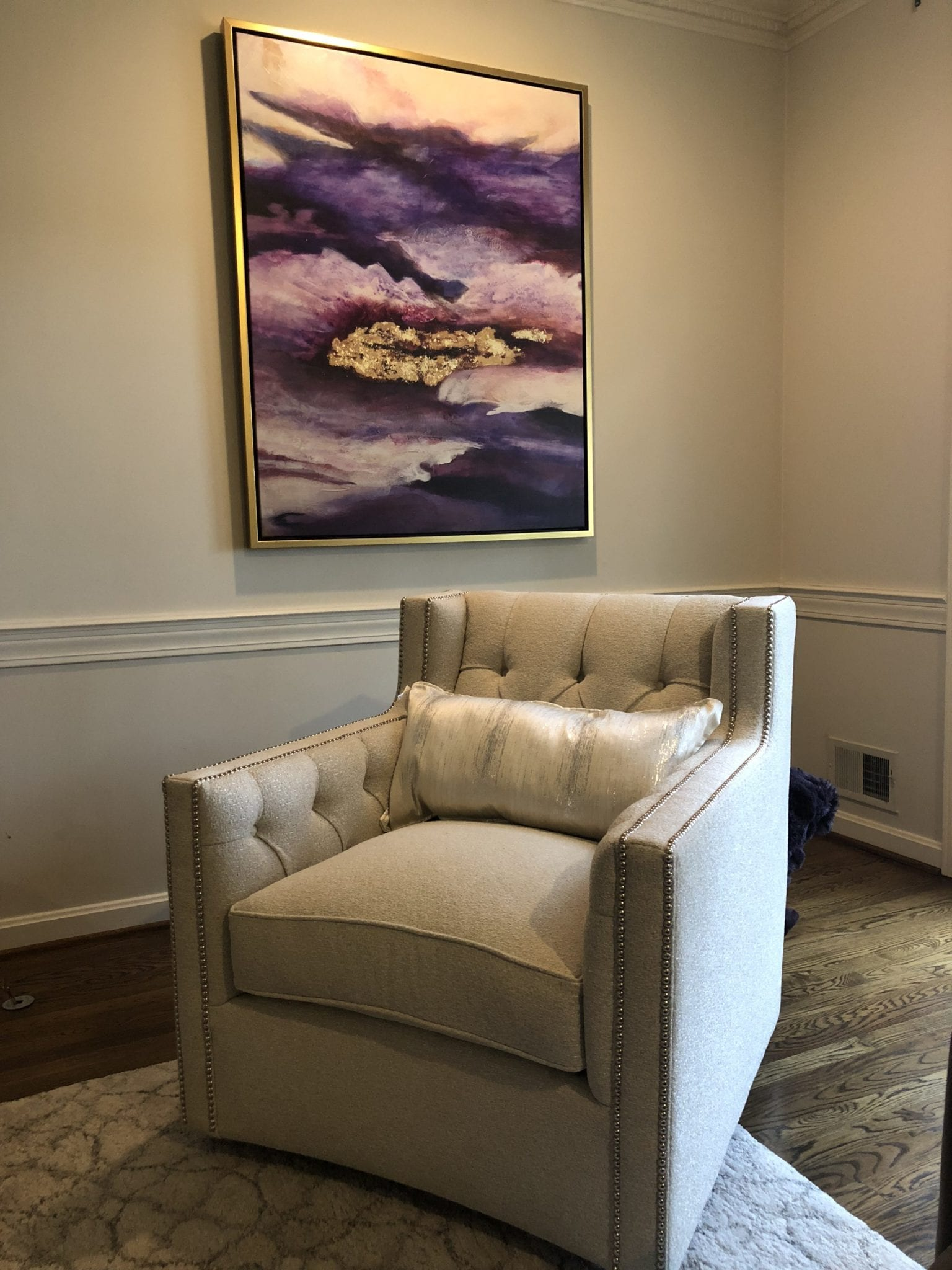 Cushioned sitting chair in front of artwork
